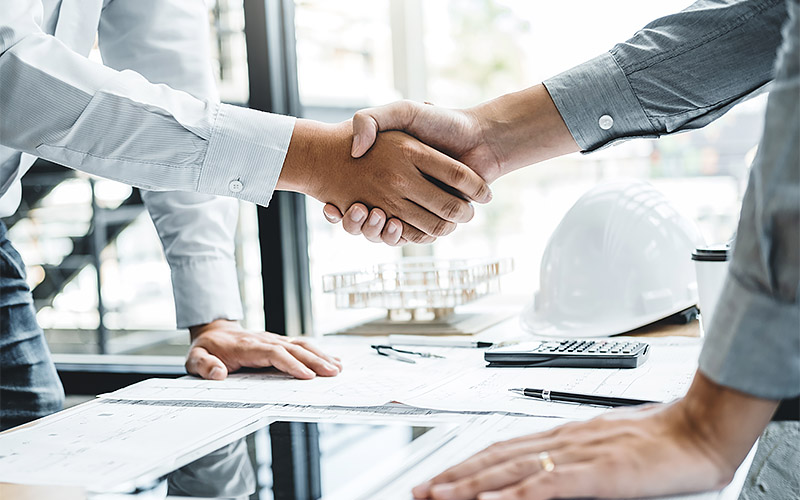 Engineer handshake meeting for architectural project and working